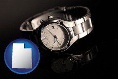 utah map icon and a wristwatch on a black background, with reflection