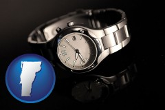 vermont map icon and a wristwatch on a black background, with reflection