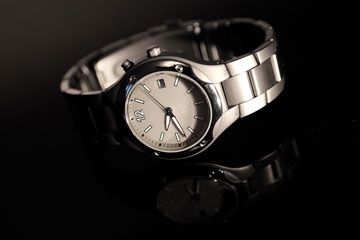 a wristwatch on a black background, with reflection